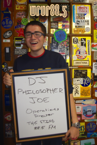 DJ Philosopher Joe (Operations Director, Sting and FM DJ) in front of the Sticker Door