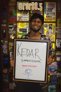 Kedar - General Manager - in front of the Sticker Door